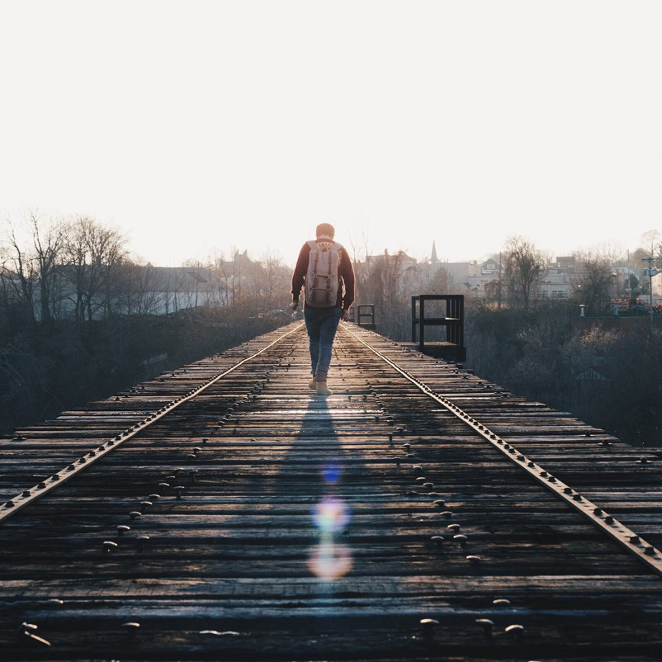 Man Walking on a Wooden Bridge